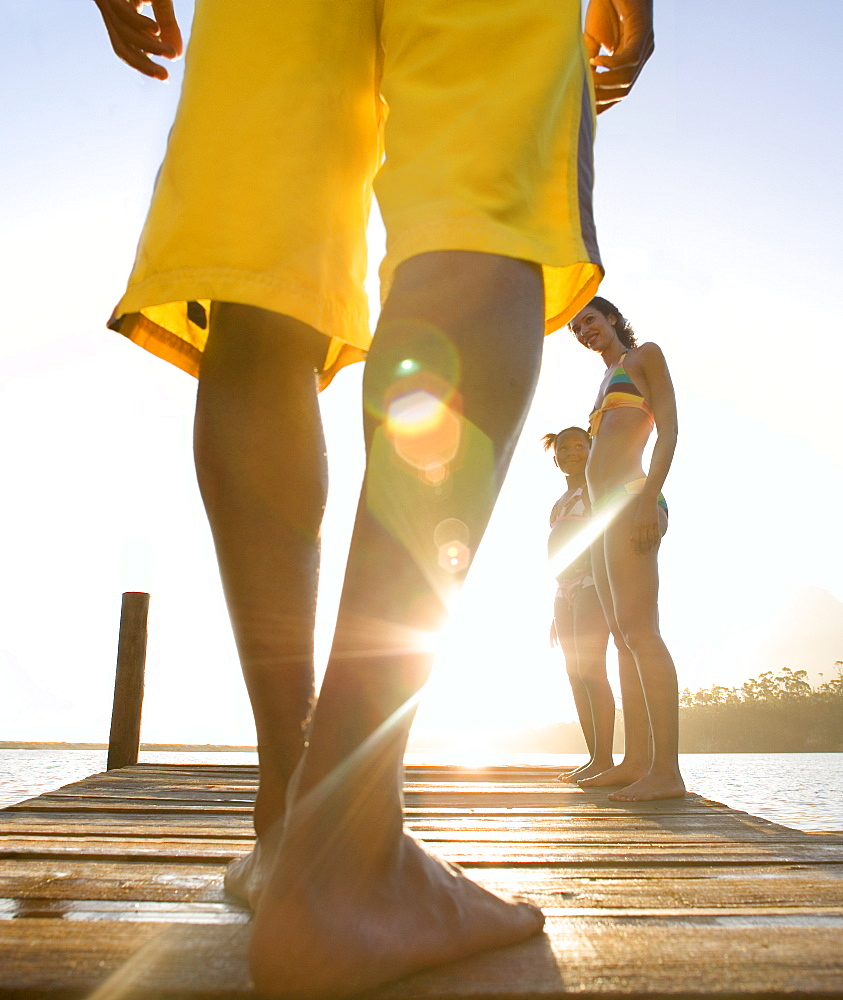 Family standing on jetty, man in yellow swimming shorts preparing to jump into lake, low-section, rear view (surface level, lens flare) - 786-2216