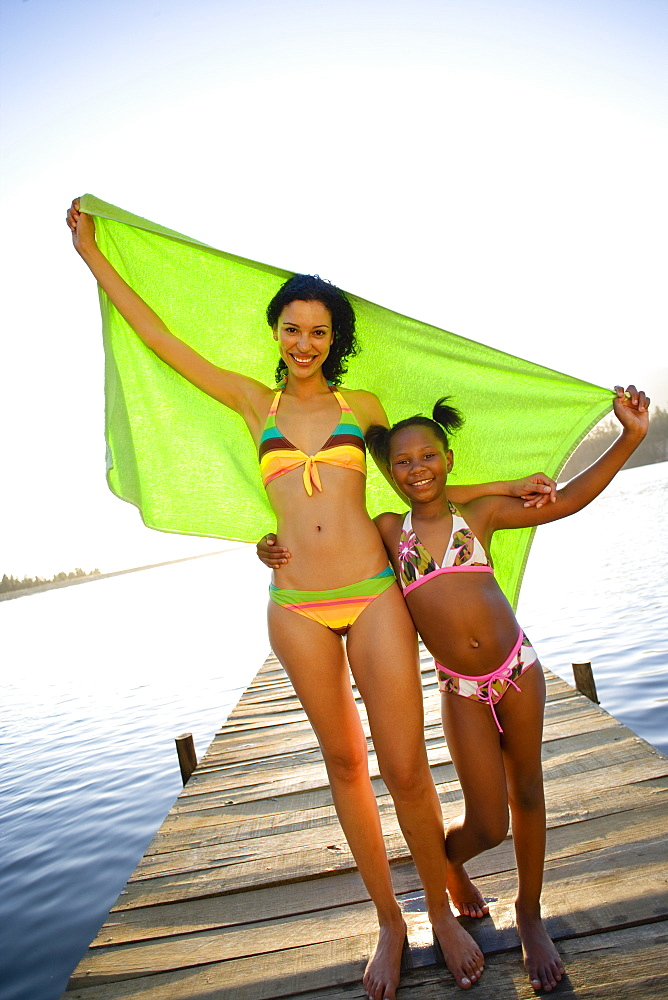 Mother and daughter (7-9) standing on lake jetty, arms around each other, holding aloft green towel, smiling, portrait (tilt)