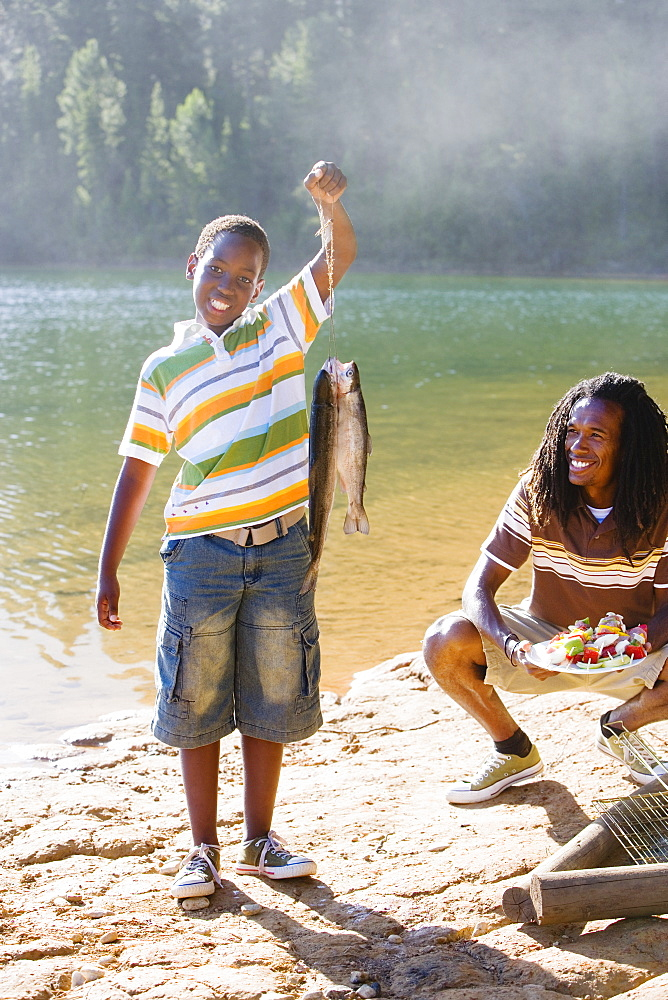 Proud boy (8-10) holding aloft fish on lakeside camping trip, father holding plate of food, smiling, portrait