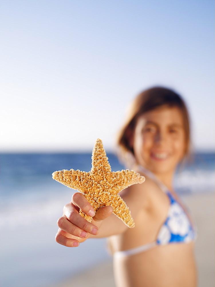 Girl (10-12) holding aloft starfish on sandy beach, smiling, portrait, focus on foreground