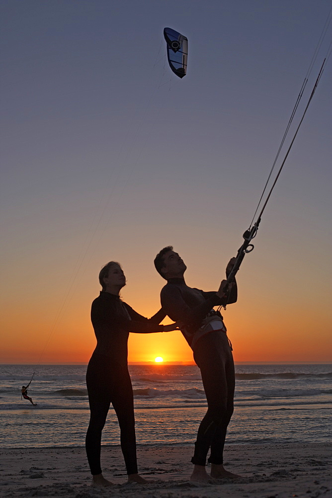 Young couple kiteboarding on beach at sunset, woman supporting man, side view (silhouette)