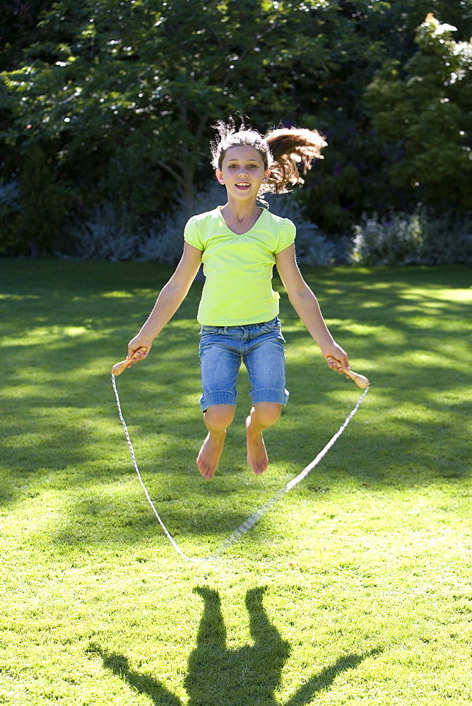 Girl (8-10) playing with skipping rope on garden lawn, smiling, front view, portrait