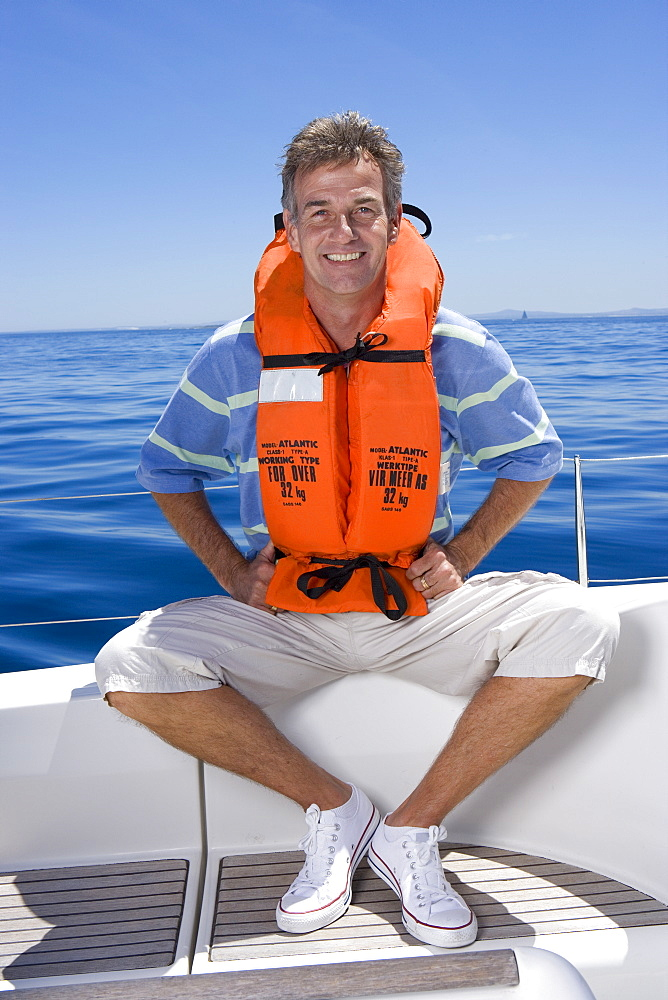 Man sitting at stern of sailing boat out at sea, wearing orange life jacket, smiling, front view, portrait