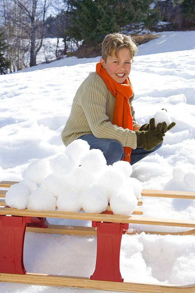 Boy (7-9) making snow ball pile on sled in snow field, smiling, portrait