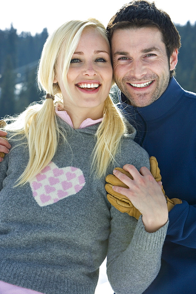 Young couple embracing in snow field, smiling, portrait, close-up