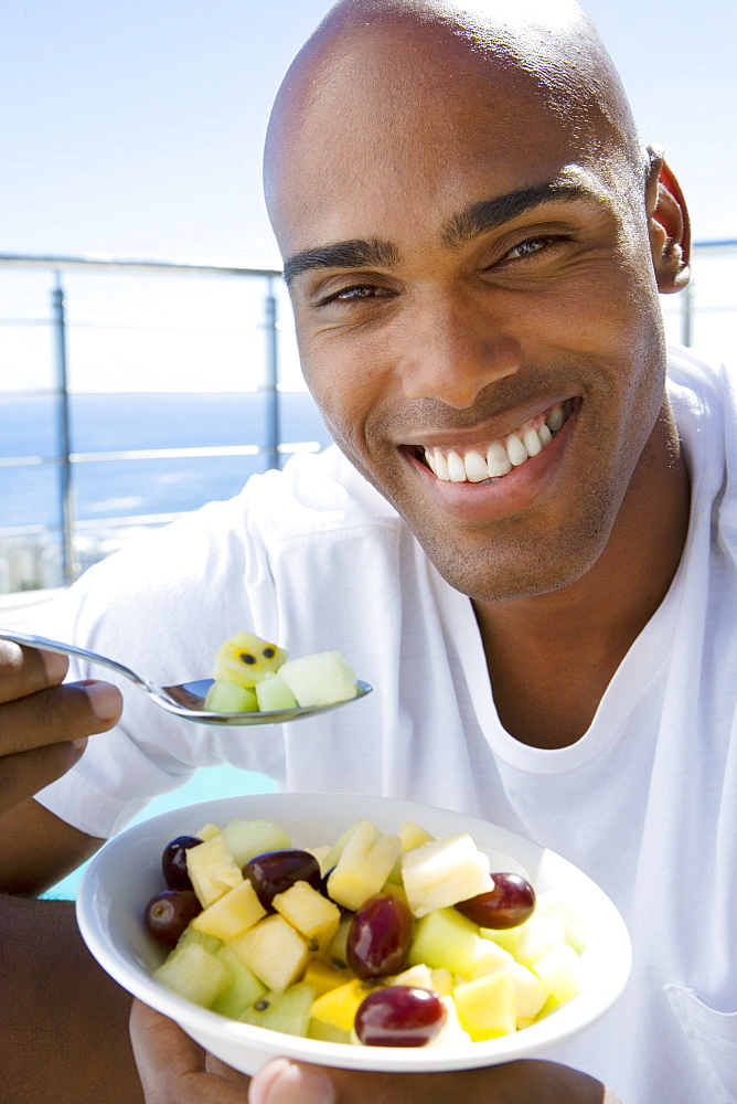 Young man holding salad outdoors, smiling, portrait, close-up