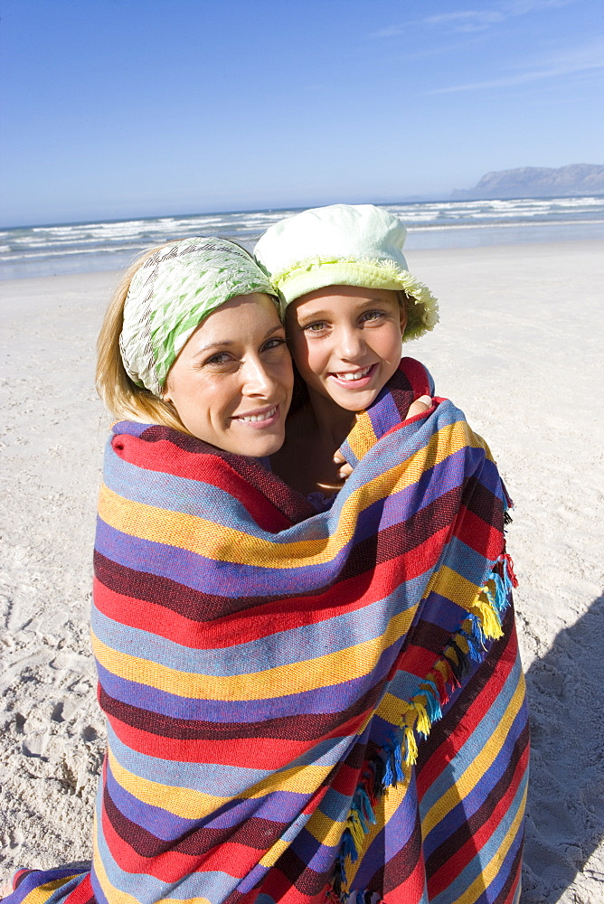 Mother and daughter (5-7) wrapped in blanket on beach, smiling, portrait, close-up