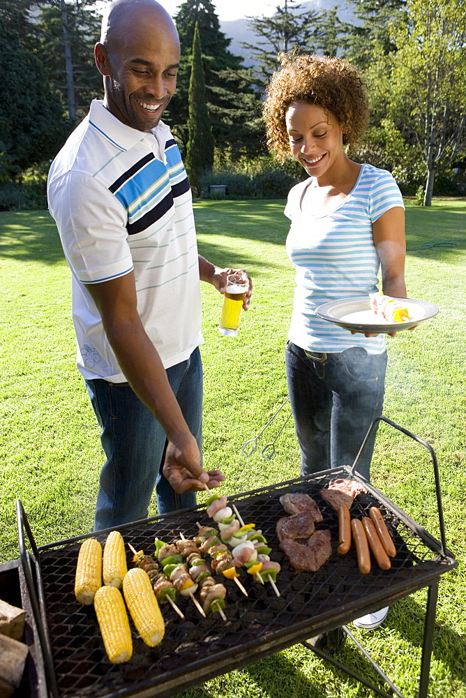 Woman with plate by man at barbeque, smiling