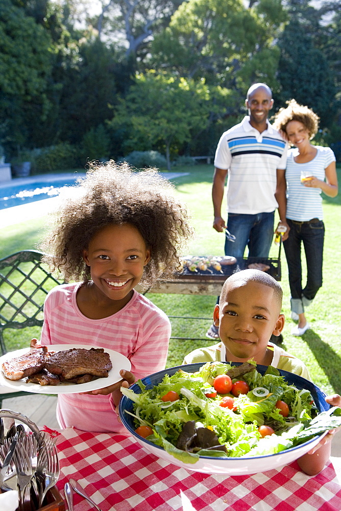 Family of four having barbeque, brother and sister (6-10) with plates of food, smiling, portrait