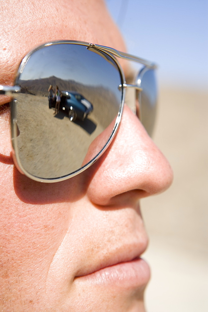 Close-up of young man, reflection of friends by car in sunglasses