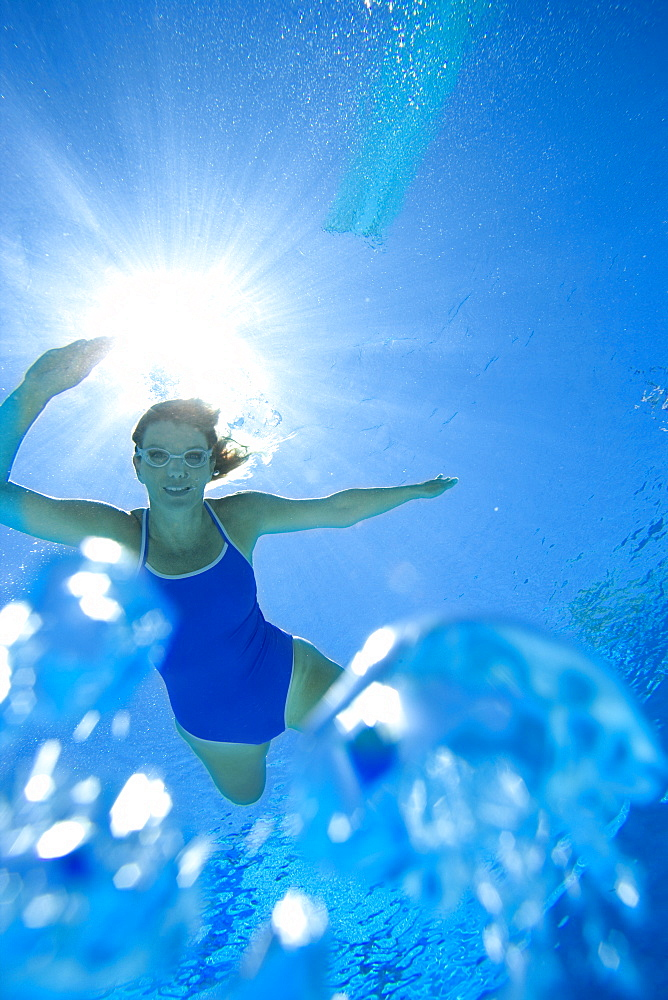 Woman in swimming pool, portrait, underwater view (lens flare) - 786-4041
