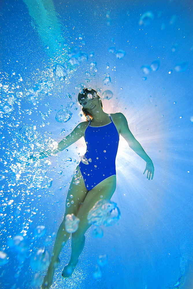 Woman in swimming pool, underwater view (lens flare) - 786-4042