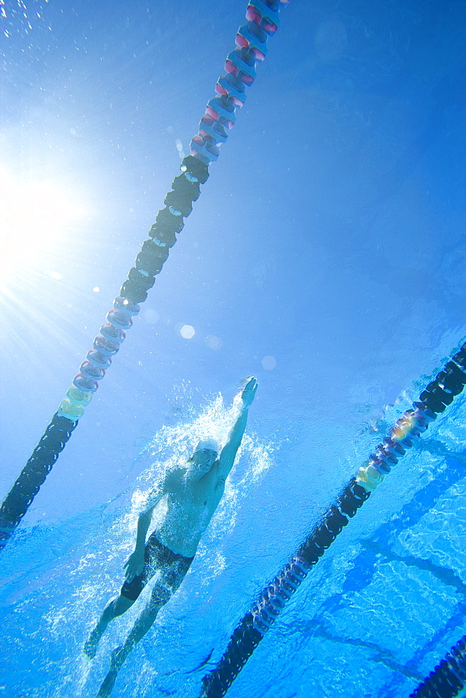 Man swimming lengths in swimming pool, underwater view (lens flare)