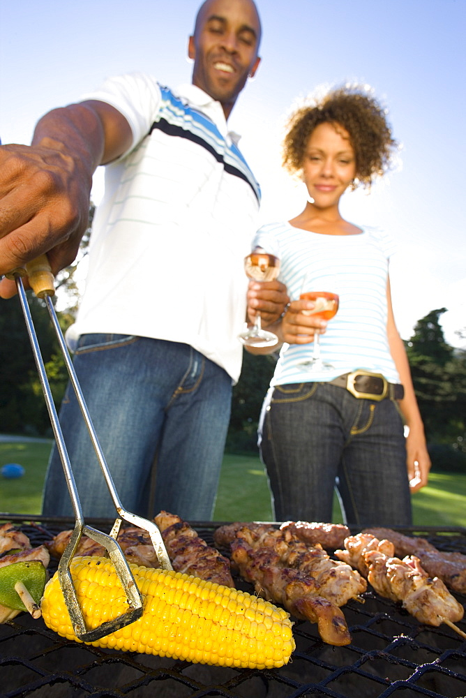 Couple having barbeque outdoors, standing by grill, low angle view