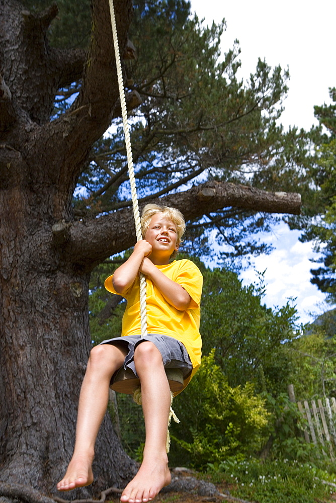 Boy (9-11) on swing, smiling, low angle view