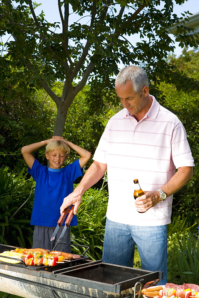 Man cooking on barbeque by son (9-11) with hands on head, smiling