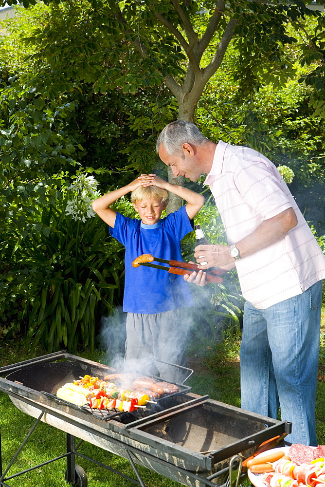 Man by barbeque showing son (9-11) sausage, smiling