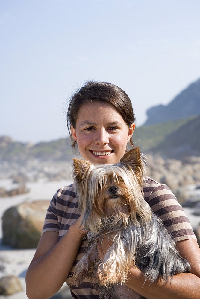 Woman holding dog on beach, smiling, portrait, close-up