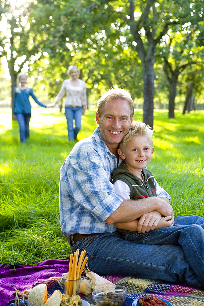 Family of four having picnic, father embracing son (7-9) smiling, portrait