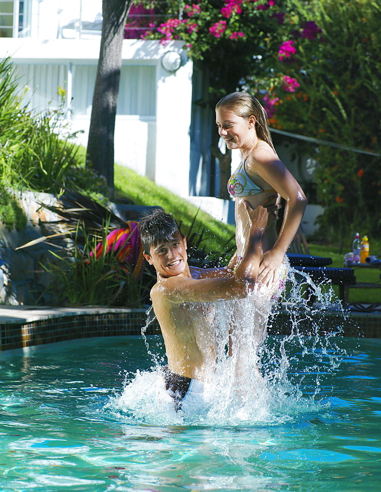 Teenage couple (15-17) playing in swimming pool, boy lifting girl out of water, smiling, side view
