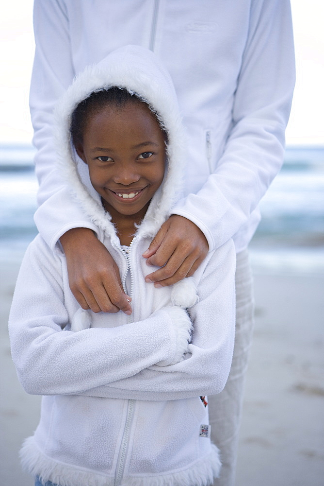 Mother with arms around daughter (7-9) on beach, smiling, portrait