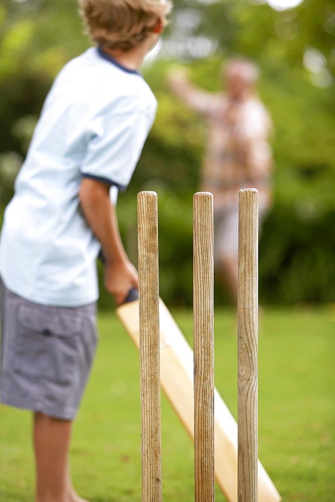 Grandfather and grandson (8-10) playing cricket, senior man bowling, focus on boy batting, rear view