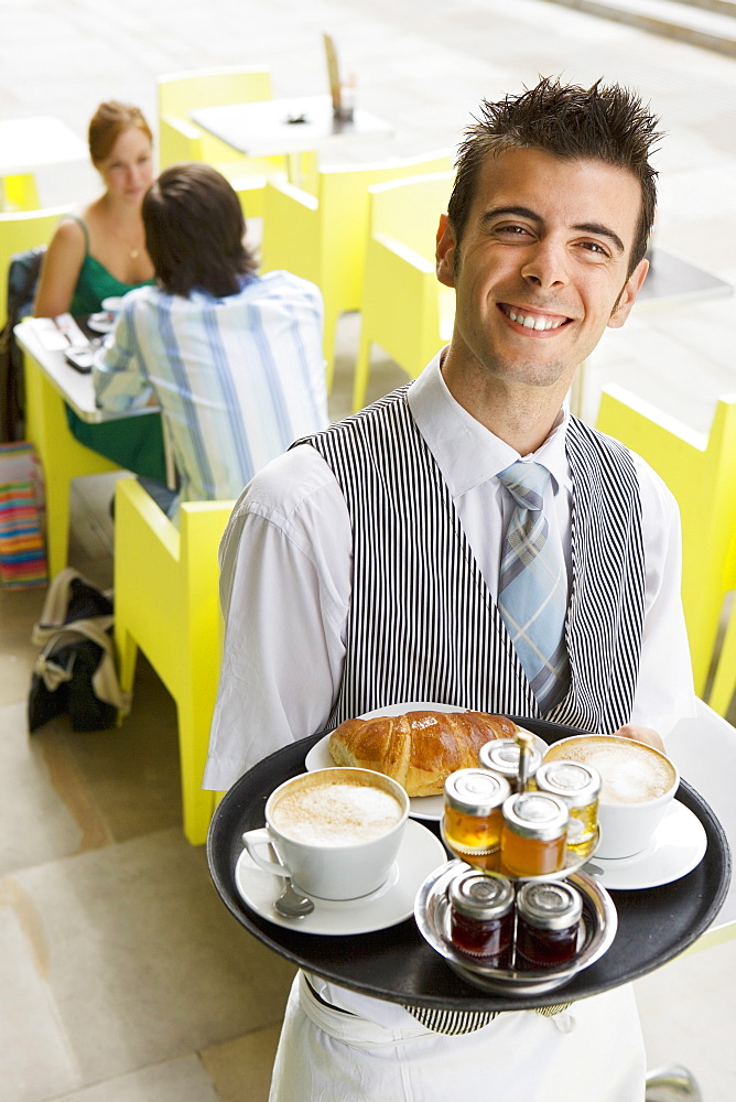 Couple sitting at pavement cafe table, focus on waiter carrying serving tray, smiling, portrait