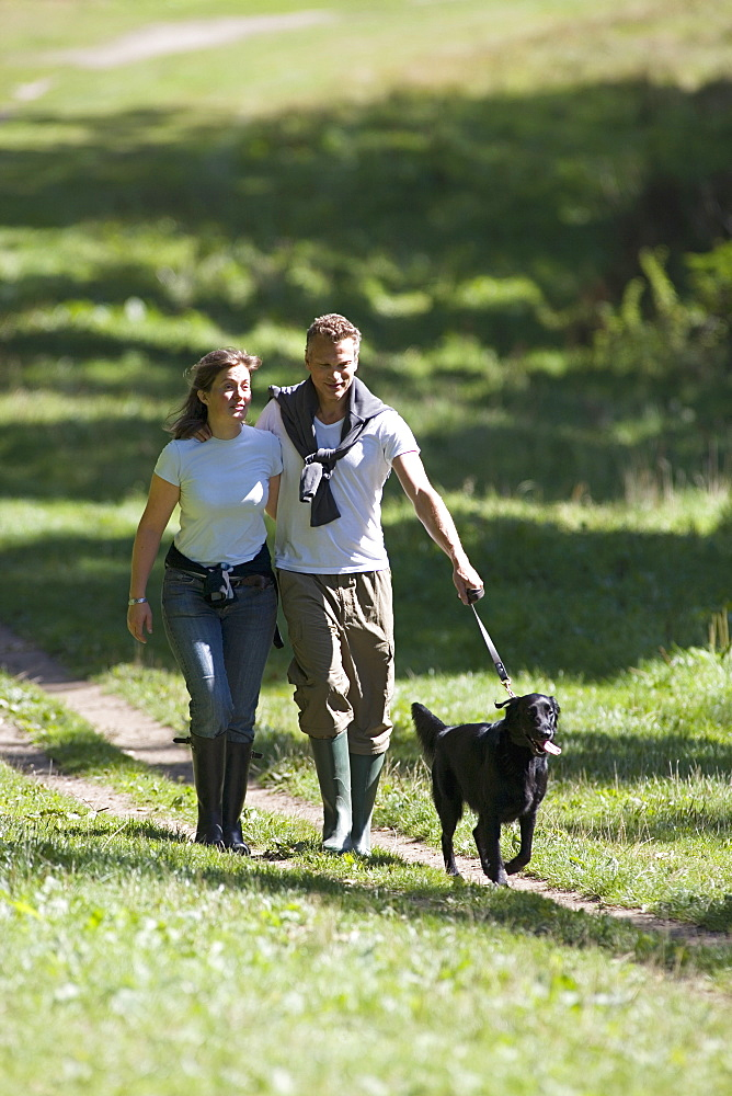 Couple walking dog in countryside, following dirt path, wearing wellington boots, smiling