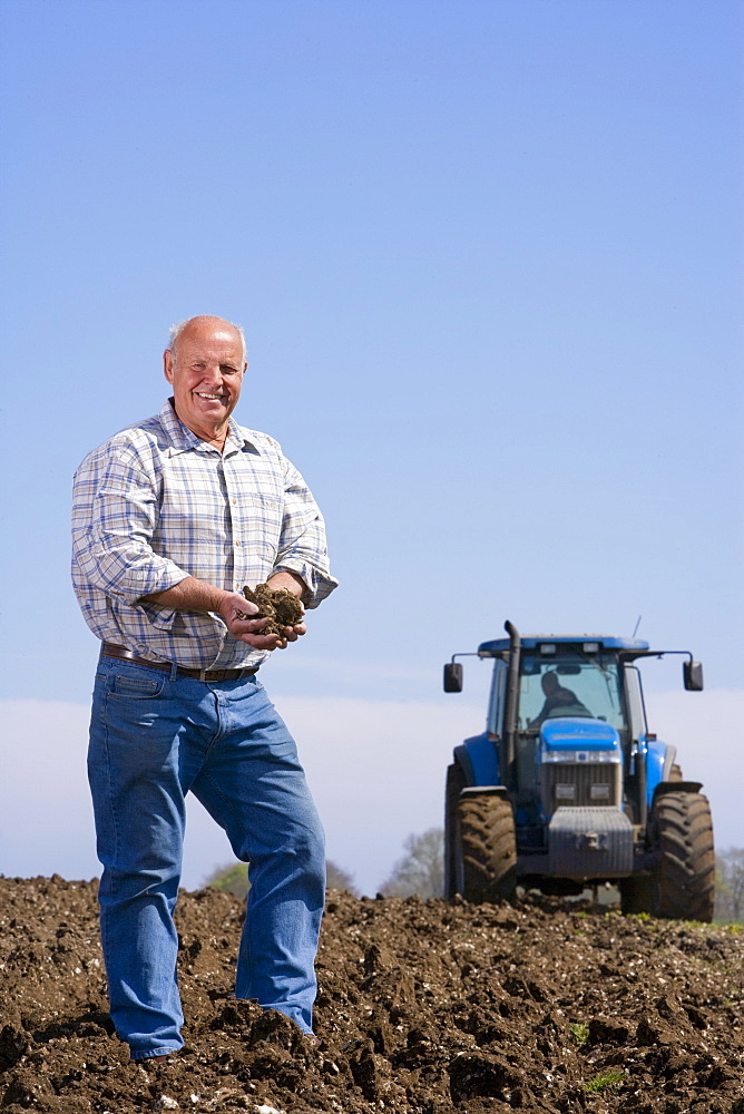 Smiling farmer cupping soil in field with tractor in background