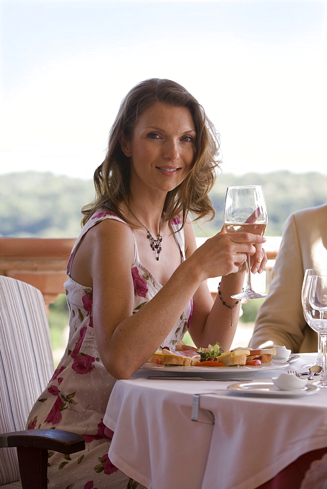 Smiling woman dining at patio table