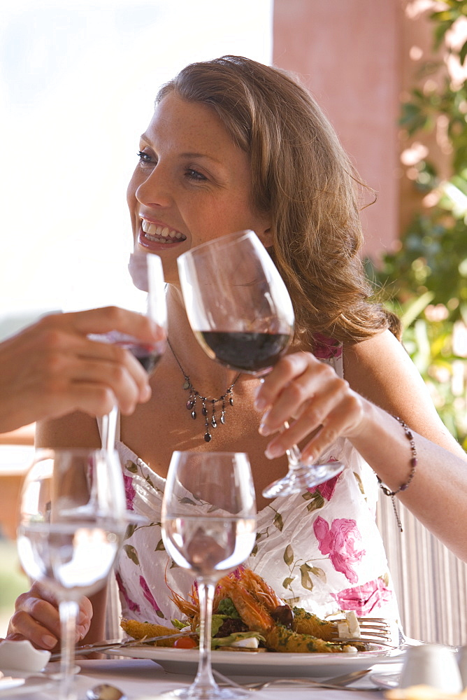 Couple toasting wine glasses at patio table