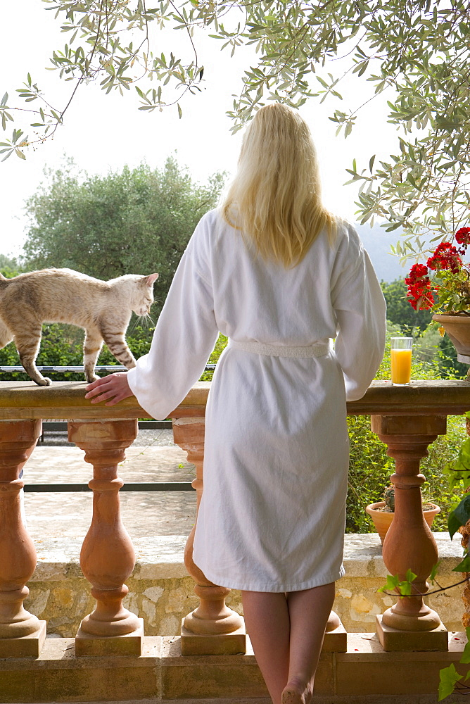 Cat next to woman in bathrobe on patio