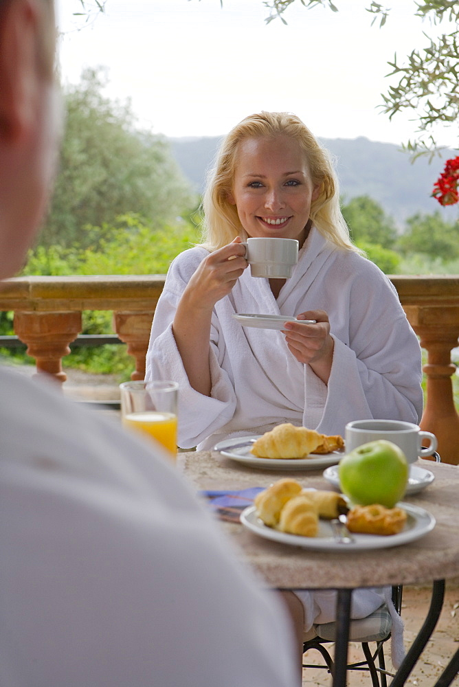 Couple in bathrobes eating breakfast on patio
