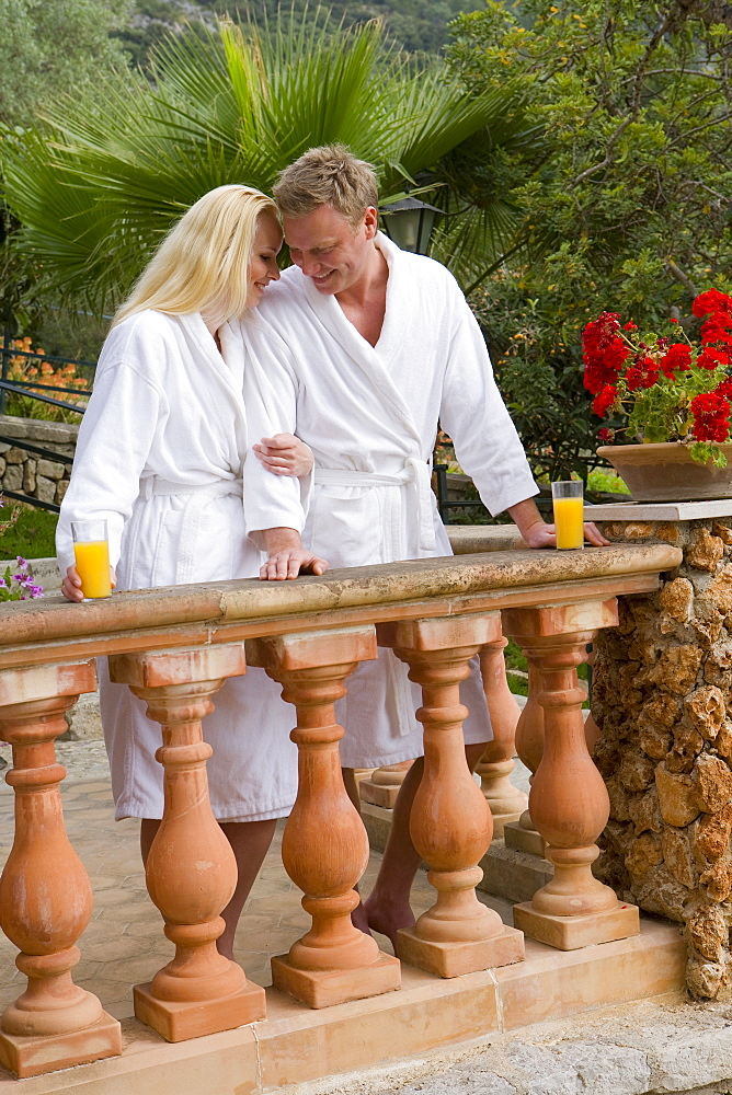 Couple in bathrobes hugging and drinking orange juice on balcony
