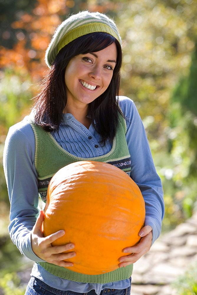 Smiling woman carrying autumn pumpkin