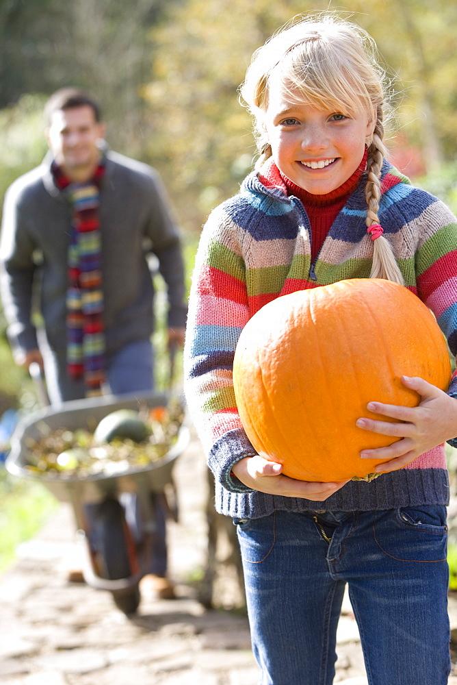 Smiling girl holding autumn pumpkin