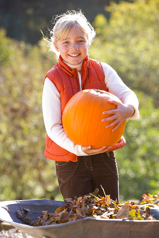 Smiling girl holding autumn pumpkin