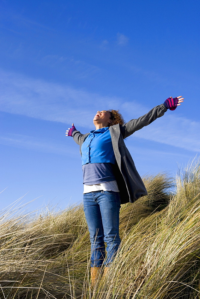 Exhilarated woman shouting on hillside