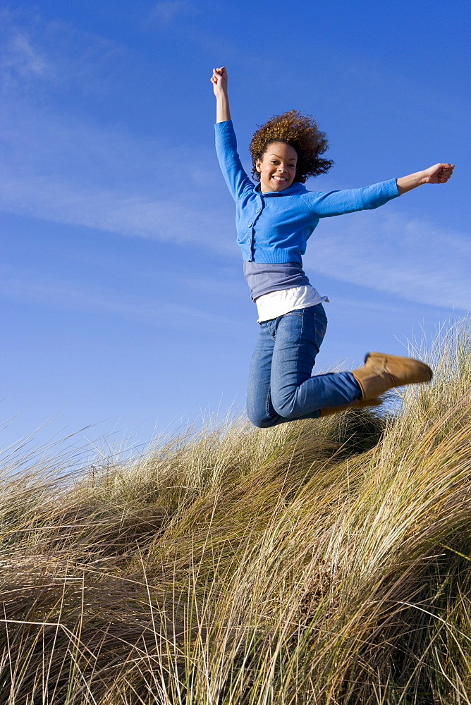 Excited woman jumping on hillside