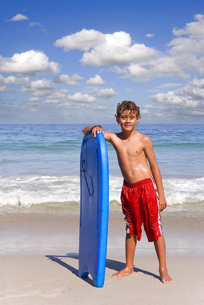 Boy standing on beach near ocean with body board