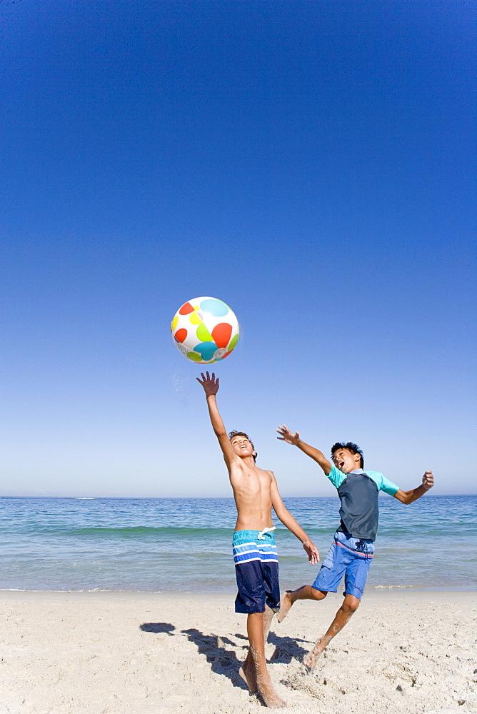 Two boys playing with beach ball on beach near ocean