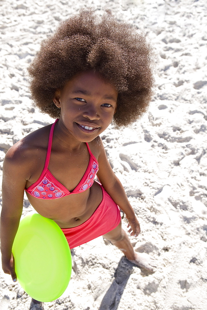 African girl in bathing suit at beach with plastic disc