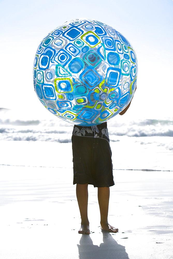 Boy holding large beach ball on beach near ocean