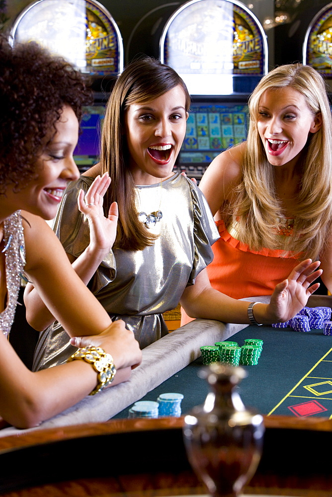 Girlfriends gambling at roulette table in casino