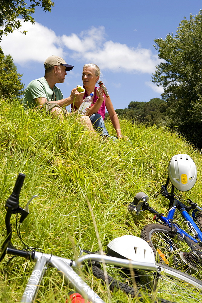 Couple eating together next to bicycles on hill