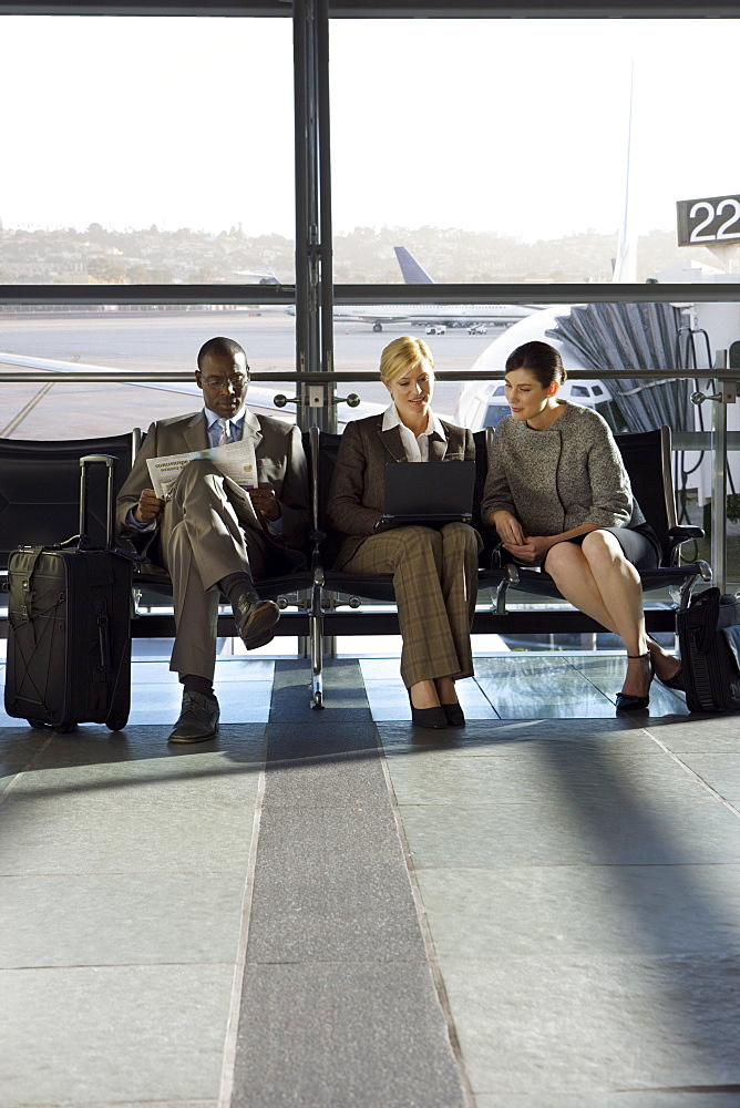 Business people in airport waiting area working together