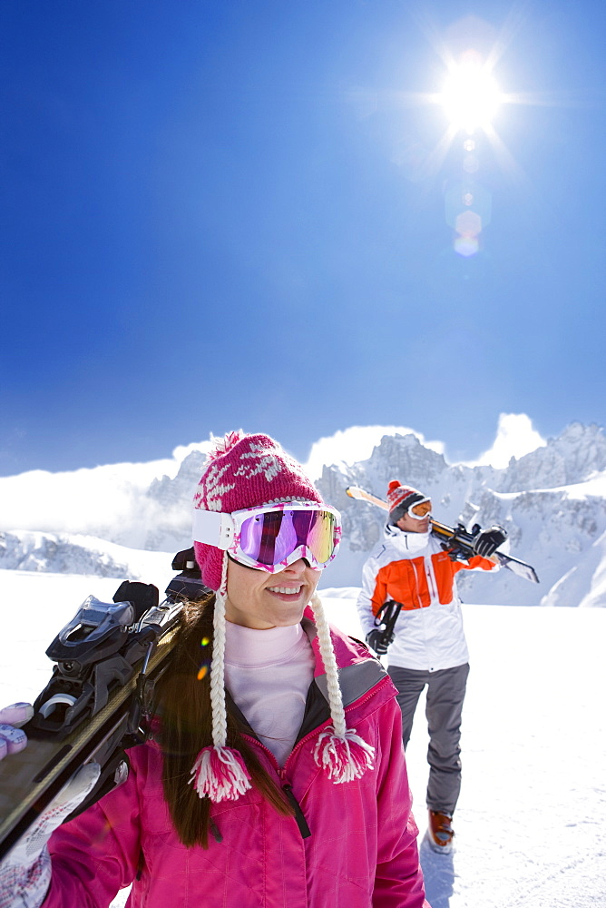 Skiers carrying skis and walking down ski slope - 786-6608