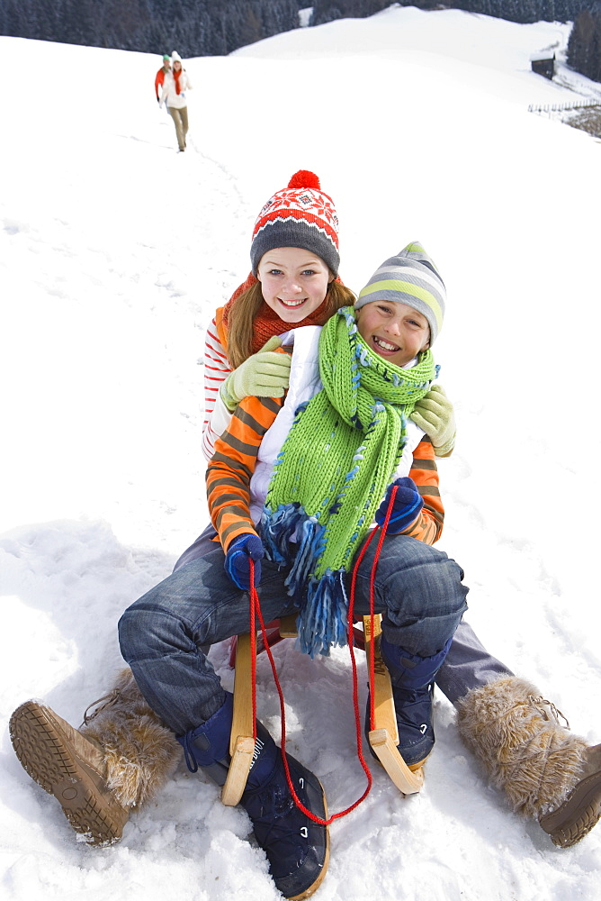 Brother and sister riding sled together in snow - 786-6616