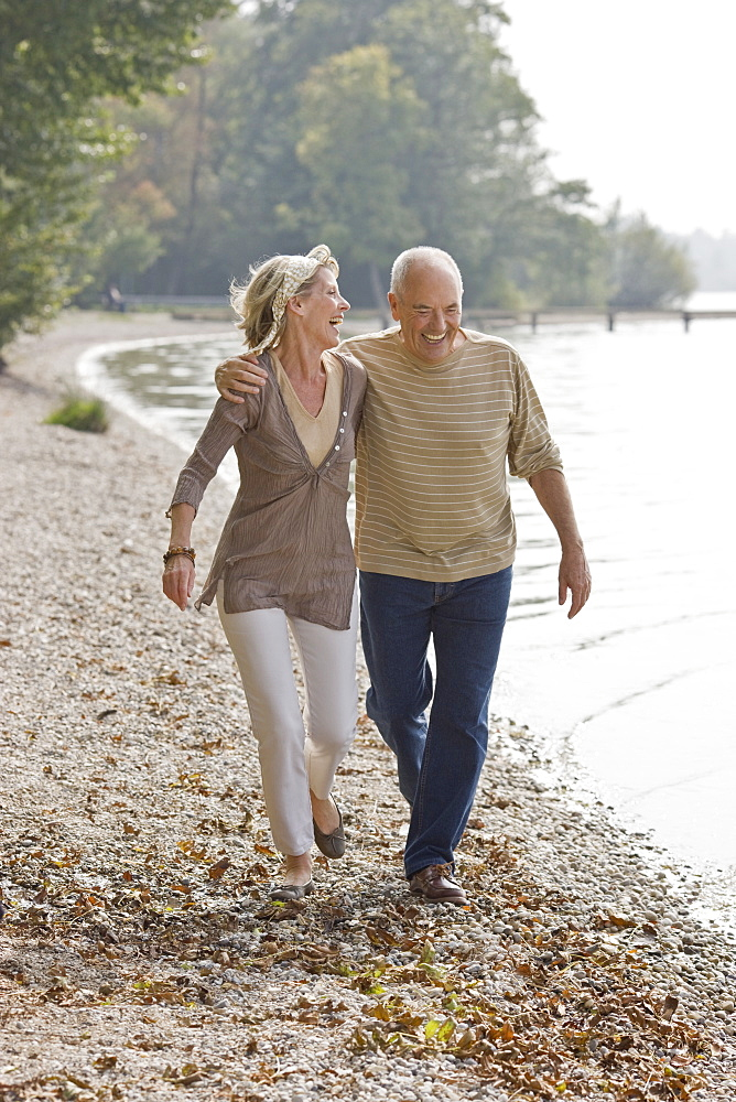 A senior couple walking along next to a lake, laughing - 786-6688