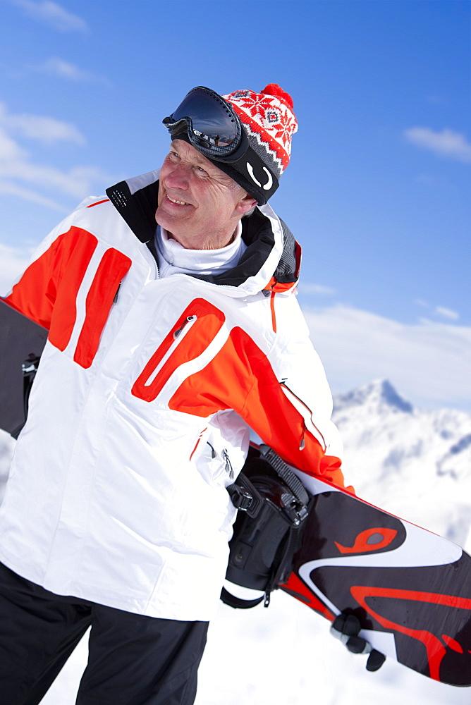 Smiling man standing holding snowboard